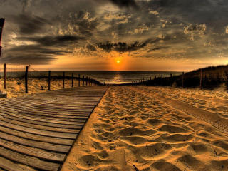 Sand And Pathway To Sea Under Cloudy Sunset wallpaper